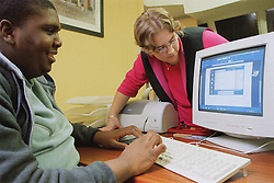 IT trainer teaching client basic IT skills including how to save documents,