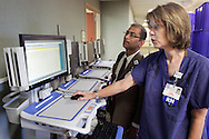 Tina Bast, a registered nurse in the Rowley Birthing Center at Orange Regional Medical Center, and Shafiq Rab, vice president of information technology and chief information officer,  look at electronic health records on a cart at Orange Regional Medical Center's new hospital in the Town of Wallkill on Thursday, July 14, 2011.