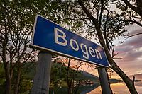 Stedsnavnskilt som markerer overgang til tettstedet Bogen i Kvæfjord kommune, Troms og Finnmark. Gullesfjorden i midnattssol i bakgrunne.