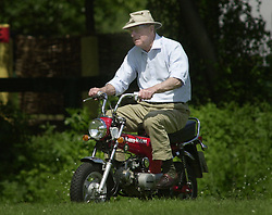The Duke of Edinburgh rides a mini motorbike around the Royal Windsor Horse Show, on his way to watch his friend Lady Romsey compete in the Carriage Driving competition.