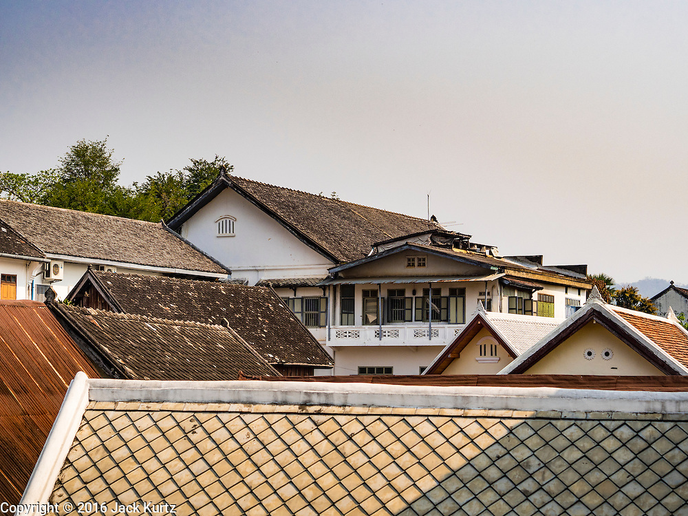 """13 MARCH 2016 - LUANG PRABANG, LAOS: The roofline of colonial era buildings that have been renovated into tourist hotels, spas and restaurants in Luang Prabang. Luang Prabang was named a UNESCO World Heritage Site in 1995. The move saved the city's colonial architecture but the explosion of mass tourism has taken a toll on the city's soul. According to one recent study, a small plot of land that sold for $8,000 three years ago now goes for $120,000. Many longtime residents are selling their homes and moving to small developments around the city. The old homes are then converted to guesthouses, restaurants and spas. The city is famous for the morning """"tak bat,"""" or monks' morning alms rounds. Every morning hundreds of Buddhist monks come out before dawn and walk in a silent procession through the city accepting alms from residents. Now, most of the people presenting alms to the monks are tourists, since so many Lao people have moved outside of the city center. About 50,000 people are thought to live in the Luang Prabang area, the city received more than 530,000 tourists in 2014.    PHOTO BY JACK KURTZ"""