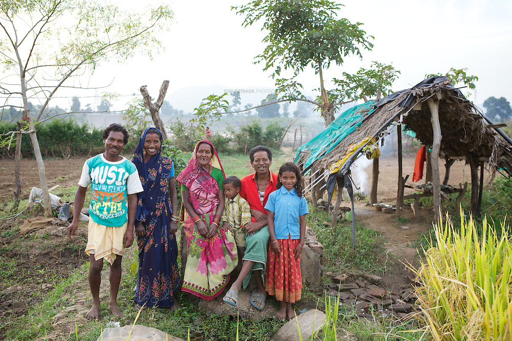 Amar Singh Patel (red shirt) and his family on their plot of irrigated land. L to R: son-in-law, Santaram; daughter, Bahura Bai; wife, Sona Bai; grandson, Limesh (age 4); Amar Singh Patel; grandaughter, Jaymati (age 11)...Amar Singh Patel, age 60 owns owns 5 acres of land, 1.5 of which is irrigated. He lives in Rathkhandi village, Bilaspur District, Chhattisgarh State with his wife Sona Bai, their daughter and son-in-law and four grandchildren...On this irrigated land, Amar Singh's family cultivate rice using the SRI technique together with a small vegetable plot. The remaining 3.5 acres are leased out to share-croppers. Amar Singh was introduced to SRI by Oxfam partners Jan Swasthya Sahyog (JSS) and began growing rice using this technique in 2007...Amar Singh's land did not always produce enough food for his family to eat. When Amar Singh was a young man, he and his family had to eat wild flowers to survive. They also had to sell their cattle, buy clothing on credit and migrate in search of work...The JSS introduced SRI to Amar Singh and others in his village. SRI is an organic system of intensively growing rice that can double crop yields double. ..Using SRI, Amar Singh and his family produce enough rice for all of their annual needs from only 1.5 acres of land. They now never go hungry...By using SRI Amar Singh never has to spend money on expensive chemicals which degrade the soil. SRI also uses less seed. With fewer inputs Amar Singh has made savings and invested these in his farm. Last year he purchased a new bullock cart. And Amar Singh's grandchildren no longer have to work the land when they should be at school as he did when he was a child. ..The JSS have recruited Amar Singh as an advocate for SRI and teach other farmers the benefits of this system of agriculture. ..Photo: Tom Pietrasik.Chhattisgarh, India.November 2012