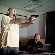 A participant of an officer accountability course, offered by the Charlotte Police Department, fires his pneumatic side arm during a simulated exercise. Each participant had to make a decision whether to use their weapon in scenarios police officers might find themselves in.