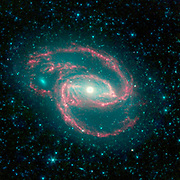 The galaxy, called NGC 1097, is located 50 million light-years away. It is spiral-shaped like our Milky Way, with long, spindly arms of stars. The 'eye' at the center of the galaxy is a black hole surrounded by a ring of stars. Spitzer.