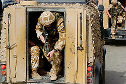 British soldiers wearing desert camouflage, Kevlar helmets and body armor, carrying SA80 assault rifles which are fitted with SUSAT sights,  exit armored Land Rover patrol vehicles, also known as a snatch, to begin a foot patrol through a market area of Basra during Op-Telic in March 2005