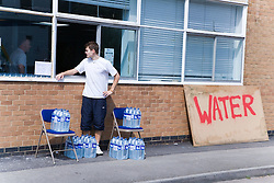 Man in charge of emergency station set up to hand out supplies of drinking water after torrential rain caused the river Severn to bust its banks and flooded the Tewkesbury area; Gloucestershire; July 2007,