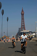 Cyclists ride up the promenade in the scorching heat with the world famous Blackpool Tower in the background as temperatures in the country are expected to soar this week on 7th September, 2021 in Blackpool, United Kingdom. Temperatures in the UK are predicted to soar to highs of 29 degrees celsius, coinciding with a rise in daycation and staycation domestic tourism in the country as a result of Covid-19 precautions that make foreign travel increasingly costly and difficult.