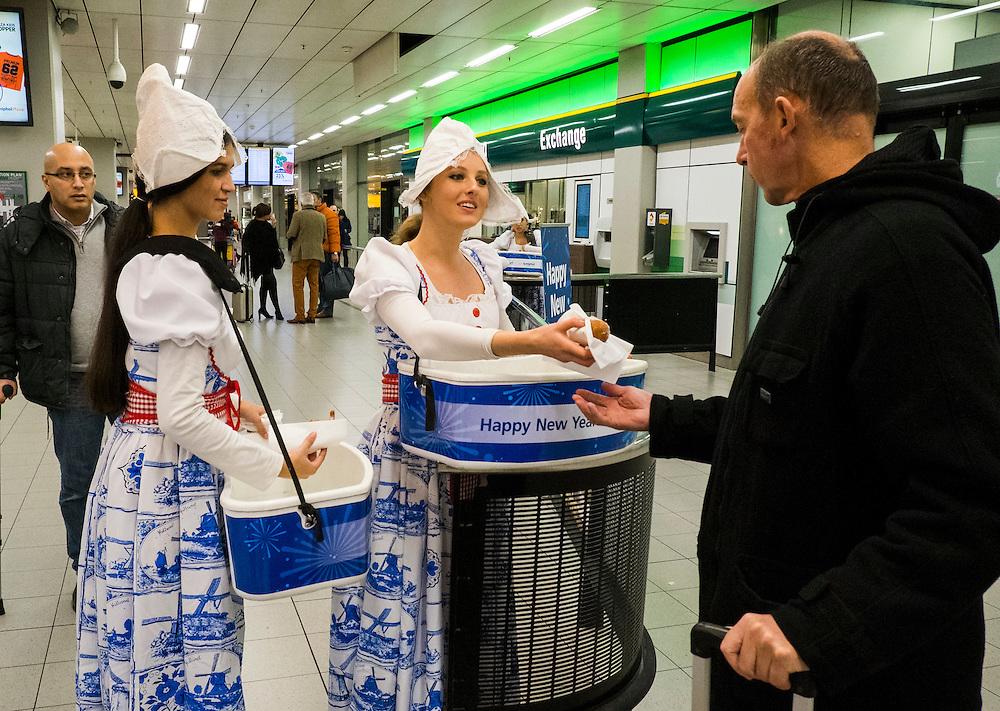 Nederland, Schiphol, 2 jan 2014<br /> Welkom voor passagiers op schiphol: een oliebol en de beste wensen namens Schiphol. Jongedames in klederdracht delen de oerhollandse lekkernij uit.<br /> Foto: Michiel Wijnbergh