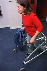Teenage girl with physical disability using walking frame to walk along college corridor,