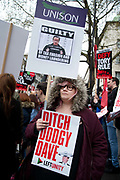 In a march organised by the Peoples Assembly, demonstrators protest  against austerity measures affecting health, education and employment, brought in by the Tory Government headed by Prime Minister David Cameron on April 16th 2016 in London, United Kingdom. Calls for Cameron's resignation followed revelations in the 'Panama Papers'. A protester holds one placard saying Ditch Dodgy Dave and another UNISON one saying Cameron guilty.
