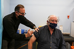 © Licensed to London News Pictures. 23/10/2021. London, UK. A NHS vaccinator, administers the Pfizer/BioNTech Covid-19 booster vaccine to John Knox at a vaccination centre in north London. Ministers are urging people who are eligible to get a Covid-19 booster jab as the experts, have reported a low uptake amid fears of further restrictions this winter as coronavirus cases rise. The Government is considering cutting the interval between booster jabs and the second dose of a Covid-19 vaccine from six month to five months. Photo credit: Dinendra Haria/LNP