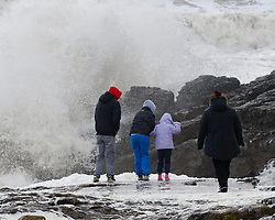 © London News Pictures. 08/02/2014. Porthcawl, UK. A family take a risk by walking on wave covered rocks in Porthcawl, wales during a gale force storm which created giant waves.. Photo credit : Graham M. Lawrence/LNP.
