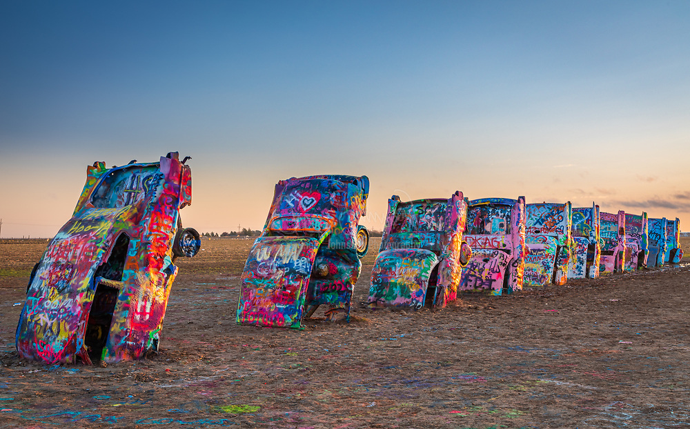 """Cadillac Ranch is a public art installation and sculpture in Amarillo, Texas, USA. It was created in 1974 by Chip Lord, Hudson Marquez and Doug Michels, who were a part of the art group Ant Farm.<br /> <br /> The installation consists of ten Cadillacs (1949-1963) buried nose-first in the ground. Installed in 1974, the cars were either older running, used or junk cars — together spanning the successive generations of the car line — and the defining evolution of their tailfins.<br /> <br /> Chip Lord and Doug Michels were architects; Marquez was an art student at Tulane University in New Orleans, Louisiana. According to Chip Lord, """"Ant Farm was founded as an alternative architectural practice, kind of an experiment in an attempt to subvert normal corporate ways of doing architecture.""""<br /> <br /> According to Marquez, """"Chip and I were living in the mountains north of San Francisco, and there was a book meant for kids left in a bar near where we lived. It was called 'The Look of Cars,' and there was something on the rise and fall of the tail fin. I didn't have a lot to do, so I just sorta drew it up. I've always loved the Cadillacs.""""<br /> <br /> The group claims to have been given a list of eccentric millionaires in 1972 in San Francisco, identifying Stanley Marsh 3 of Amarillo amongst those who might be able to fund one of their projects and submitted it to him. Marsh's response began """"It's going to take me awhile to get used to the idea of the Cadillac Ranch. I'll answer you by April Fool's Day. It's such an irrelevant and silly proposition that I want to give it all my time and attention so I can make a casual judgment of it."""""""
