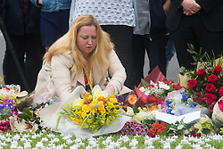 Parliament Square, Westminster, London, June 17th 2016. Following the murder of Jo Cox MP friends and members of the public lay flowers, light candles and leave notes of condolence and love in Parliament Square, opposite the House of Commons. PICTURED: A woman lays flowers in the ever-growing array of floral tributes.