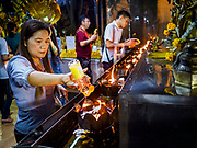 31 DECEMBER 2018 - BANGKOK, THAILAND: A woman makes merit by pouring oil into oil lamps during New Year's Eve prayers and meditation at Wat Pathum Wanaram in central Bangkok. Many Thais go to temples to meditate and pray on New Year's Eve.    PHOTO BY JACK KURTZ