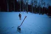 Judd MacRae walks back from the outhouse, past a large snow shovel, outside the backcountry North Pole Hut, San Juan Mountains, Colorado.