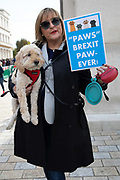 A woman with her dog and a placard reading Paws Brexit Paw-Ever joins pet owners to take part in an anti Brexit Wooferendum rally on October 07, 2018 in London, England to protest against Britain leaving the European Union.