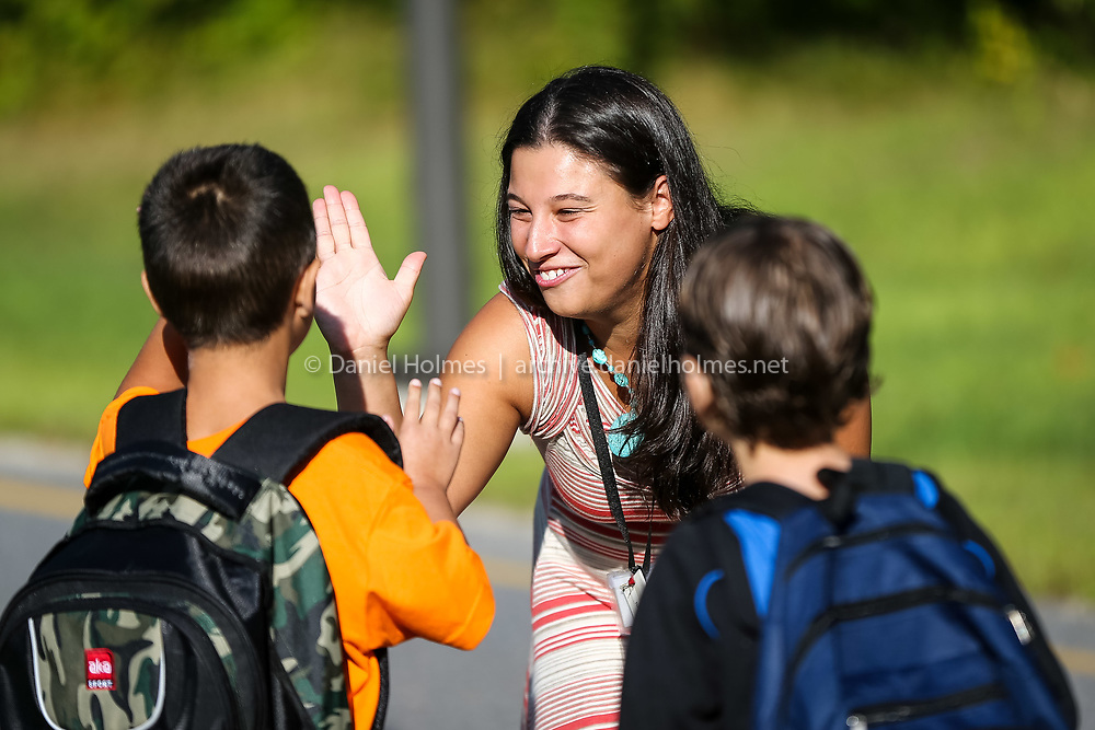 (8/26/14, MILFORD, MA) Teacher Katelyn Bruyere high-fives students as they arrive on the first day of school at Brookside Elementary School in Milford on Tuesday. Daily News and Wicked Local Photo/Dan Holmes