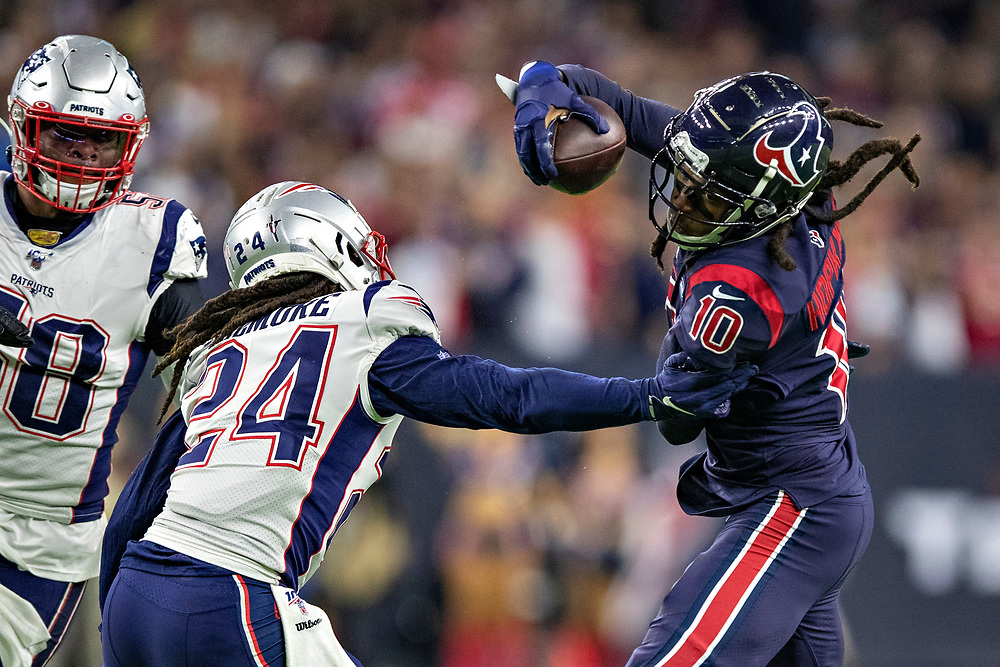 HOUSTON, TX - DECEMBER 1:  DeAndre Hopkins #10 of the Houston Texans catches a pass during the second half of a game and is tackled by Stephon Gilmore #24 of the New England Patriots at NRG Stadium on December 1, 2019 in Houston, Texas.  The Texans defeated the Patriots 28-22.  (Photo by Wesley Hitt/Getty Images) *** Local Caption *** DeAndre Hopkins; Stephon Gilmore