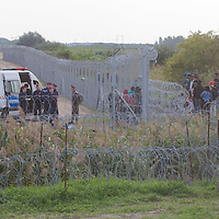 Army soldiers and police officers stand guard and send migrants away as another group of illegal migrants are being detained after crossing the razor wire fence on the border between Serbia and Hungary near Roszke (about 174 km South of capital city Budapest), Hungary on September 15, 2015. ATTILA VOLGYI