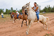 """09 SEPTEMBER 2007 -- ST. MICHAELS, AZ: The start of the """"Cowhand Race"""" at a traditional Navajo Horse Race in the summit area of the Navajo Indian reservation about 10 miles west of St. Michaels, AZ. Traditional horse racing is making a comeback on the Navajo reservation. The races are run on improvised courses that vary depending on the local terrain. Use of saddles is optional (except in the """"Cowhand Race"""" which requires a western style saddle) and many jockeys ride bareback. In the Cowhand Race, jockeys ride bareback for the first half, then saddle their horse, using a western style saddle, and complete the race in the saddle. The distances vary from one mile to as long as thirty miles. Traditional horse races were common until the 1950's when they fell out of favor, but there has been a resurgence in traditional racing since the late 1990's and now there is a traditional horse racing circuit on the reservation. The race was organized by the Begay family of Steamboat, AZ and run on private land about three miles from a paved road.  Photo by Jack Kurtz"""