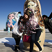 """Chinese tourists pose for a picture in front of giant Russian """"Matryoshka"""" dolls in Manzhouli, a Chinese boomtown on the China-Russia border. The town has grown from a smaller village just two decades ago to a town of 200,000 people, and its economy is driven by trade with Russia across the border."""