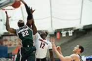 29 MAR 2015: Branden Dawson (22) of Michigan State University grabs a rebound in front of Mangok Mathiang (12) of the University of Louisville during the 2015 NCAA Men's Basketball Tournament held at the Carrier Dome in Syracuse, NY. Michigan State defeated Louisville 76-70 to advance. Brett Wilhelm/NCAA Photos