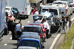 © Licensed to London News Pictures. 23/07/2016<br /> People standing on the M20 WAITING  FOR THE TRAFFIC TO MOVE.<br /> M20 traffic near the Euro Tunnel Service Station at the back of a very very long queue into Dover, kent.<br /> Dover bound traffic ON THE  M20 in Kent at Junction 11A AND 12.  Queueing traffic because of very long delays at French border contol. <br /> <br /> <br /> (Byline:Grant Falvey/LNP)
