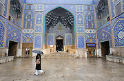 A woman carrying an umbrella in the light snow and rain, passes by the beautifully tiled private mosque called Sheikh Lotfollah Mosque.  Imam Square, Isfahan, Iran. (Also referred to as Emam Square).  (Imam Square is also called Naghsh-i Jahan Square).