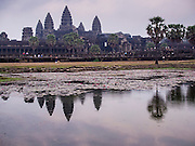 "14 MARCH 2105 - SIEM REAP, SIEM REAP, CAMBODIA: Angkor Wat is reflected in the reflecting pool in front of the temple. The area known as ""Angkor Wat"" is a sprawling collection of archeological ruins and temples. The area was developed by ancient Khmer (Cambodian) Kings starting as early as 1150 CE and renovated and expanded around 1180CE by Jayavarman VII. Angkor Wat is now considered the seventh wonder of the world and is Cambodia's most important tourist attraction.   PHOTO BY JACK KURTZ"