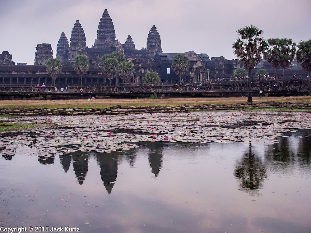 """14 MARCH 2105 - SIEM REAP, SIEM REAP, CAMBODIA: Angkor Wat is reflected in the reflecting pool in front of the temple. The area known as """"Angkor Wat"""" is a sprawling collection of archeological ruins and temples. The area was developed by ancient Khmer (Cambodian) Kings starting as early as 1150 CE and renovated and expanded around 1180CE by Jayavarman VII. Angkor Wat is now considered the seventh wonder of the world and is Cambodia's most important tourist attraction.   PHOTO BY JACK KURTZ"""