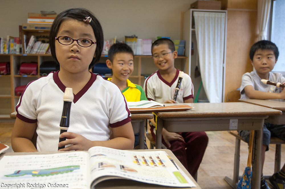 Children listen to the instructions of the teacher during a music class at Hakusan Primary School in Kamaishi, Japan.
