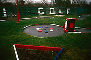 An abandoned Crazy Golf course lies broken and sad in a field at the northwestern seaside resort of Southport. It is a dark winter's day and off-season when no tourists, let alone locals have ventured out to this otherwise popular summer resort for those away from the towns and cities such as nearby Liverpool. The word Golf is peeling and fading on a broken green fence and the course that was once freshly painted woodwork attracted families for an hour's fun. The rapid growth of Southport largely coincided with the Industrial Revolution and the Victorian era. Town attractions include Southport Pier, the second longest seaside pleasure pier in the British Isles. Now it is a sad indictment of the decline of many English towns and only the green grass looks fresh and healthy.
