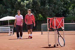 Two young men walking on tennis court, Bavaria, Germany