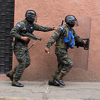 Soldiers run through central Tegucigalpa, ready to shoot teargas at protestors.