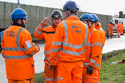 Harefield, UK. 8 February, 2020. HS2 engineers discuss how to prevent environmental activists from blocking tree felling works for the high-speed rail project. The activists, based at a series of wildlife protection camps in the area, used a variety of tactics to ensure that the tree felling work, for which road and rail closures had been implemented, was not carried out for the duration of the weekend for which it had been scheduled.
