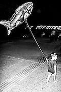 September 2015. Thessaloniki. Kid walks with his shark ballon across the Thessaloniki's seafront at night.