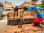01 MARCH 2017 - BUNGAMATI, NEPAL: Workers deliver bricks to a site to rebuild homes destroyed in the 2015 earthquake. Recovery seems to have barely begun nearly two years after the earthquake of 25 April 2015 that devastated Nepal. In some villages in the Kathmandu valley workers are working by hand to remove ruble and dig out destroyed buildings. About 9,000 people were killed and another 22,000 injured by the earthquake. The epicenter of the earthquake was east of the Gorka district.     PHOTO BY JACK KURTZ