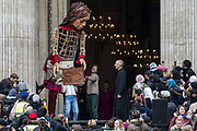 Little Amal, a giant puppet of a Syrian refugee girl fleeing conflict, presents a wood carving of a ship at sea from St Pauls birthplace at Tarsus in Turkey to Dr David Ison, the dean of St Pauls Cathedral, on 23rd October 2021 in London, United Kingdom. The 3.5-metre puppet is nearing the end of an 8,000 km journey from the Turkish-Syrian border to Manchester in support of refugees.