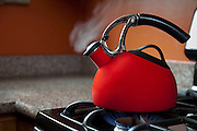 A red shiny teapot in a kitchen boils water.