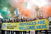 Demonstrators with smoke bombs and a banner reading Refugees Are Welcome Here at Anti-racism Day demonstration led by Stand Up To Racism on 19th March 2016 in London, United Kingdom. Stand Up To Racism has led some of the biggest anti-racist mobilisations in Britain of the last decade, making a stand protesting against racism, Islamophobia, anti-Semitism and(photo by Mike Kemp/In Pictures via Getty Images)