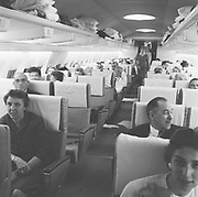 """Y-591002-08. """"707 jet. Pan Am first flight to Honolulu. Chuck White. October 2, 1959"""" (Portland International Airport, Portland Columbia Airport) caption published: """"SEATS. This view from rear entrance of Pan Am's Boeing jet 707-321 shows six-abreast seating with accommodates 87 coach passengers. First class cabin forward seats an additional 34 persons."""""""