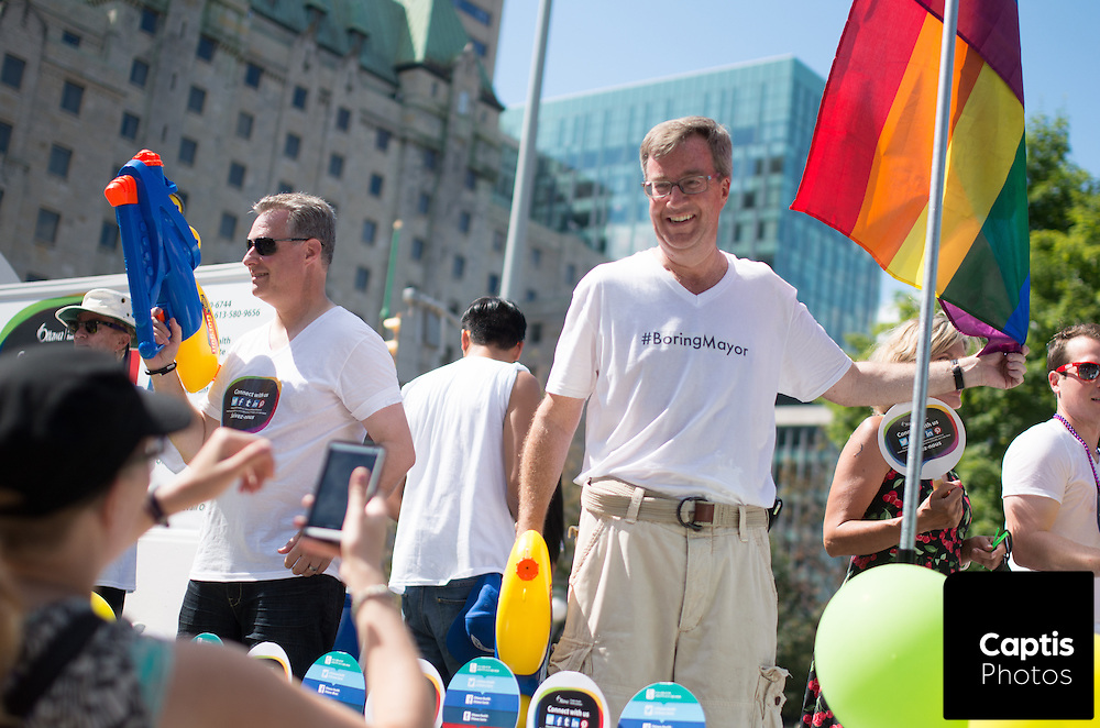 Ottawa mayor Jim Watson smiles for photos while riding a float in the parade. August 24, 2014.