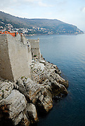 City wall and foundations jutting out of sea, Dubrovnik old town, Croatia