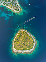 Aerial view of isolated Lefkada island next to mainland with speedboat passing, Greece.