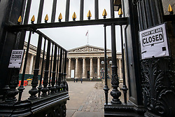 """© Licensed to London News Pictures. 19/03/2020. London, UK. """"Sorry we are closed"""" signs are attached to a gate outside the British Museum in London, which has closed to visitors because of the Coronavirus outbreak. The government has announced a series of measures designed to slow the spread of the virus, which is now spreading more rapidly in the capital than in other parts of the country. Photo credit: Rob Pinney/LNP"""