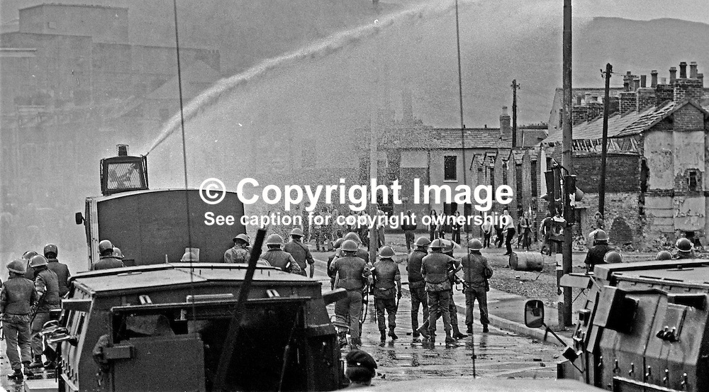 British soldiers use a water canon against rioters on the Lower Falls Road area of Belfast. The rioting broke out following a People's Democracy march which was prevented by soldiers and police from entering the city centre in Belfast, N Ireland. The march was in support of PD leaders Michael Farrell and Tony Canavan who were on hunger strike seeking political status in Belfast's Crumlin Road Jail.  29 July 1973, 197307290522f<br /> <br /> Copyright Image from Victor Patterson, Belfast, UK<br /> <br /> t: +44 28 9066 1296 (from Rep of Ireland 048 9066 1296)<br /> m: +44 7802 353836<br /> e: victorpattersonbelfast@gmail.com<br /> <br /> www.images4media.com<br /> <br /> Please see my full Terms and Conditions of Use at https://www.images4media.com/p/terms-conditions - it is IMPORTANT that you familiarise yourself with them.<br /> <br /> Images used online incur an additional cost. This cost should be agreed in writing in advance. Online images must be visibly watermarked i.e. © Victor Patterson or that of the named photographer within the body of the image. The original metadata must not be deleted from images used online.<br /> <br /> This image is only available for the use of the download recipient i.e. television station, newspaper, magazine, book publisher, etc, and must not be passed on to a third party. It is also downloaded on condition that each and every usage is notified within 7 days to victorpattersonbelfast@gmail.com.
