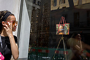 A woman passes the luxury shop window of Louis Vuitton featuring their exclusive range of bags with the face of Leonardo da Vinci's Mona Lisa - a collaboration with the artist Jeff Koons and part of work entitled The Masters Collection, on 5th July 2017, on New Bond Street, in London England.