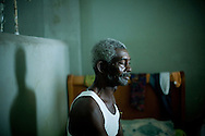 Nicolas Bazile, 74, suffers from high blood pressure and is paralyzed on his right side.  His daughter spends afternoons by his side in the Department of Internal Medicine at University Hospital in Port-au-Prince, Haiti.
