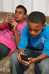 Teenagers texting and playing games on mobile phones
